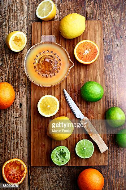 fresh fruit being squeezed on chopping board