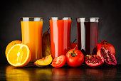 Fresh Pressed Juice Drink from Fruits and Tomato on Dark Background