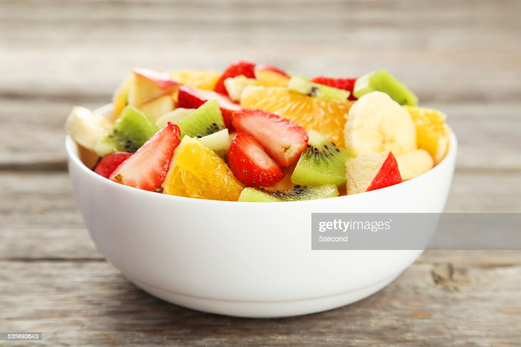 Fresh fruit salad on grey wooden background : Stockfoto