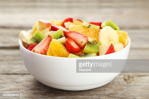 Fresh fruit salad on grey wooden background : Bildbanksbilder