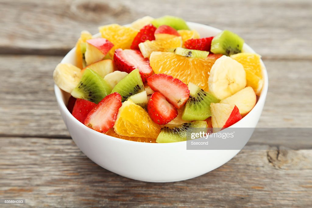 Fresh fruit salad on grey wooden background : Stock Photo