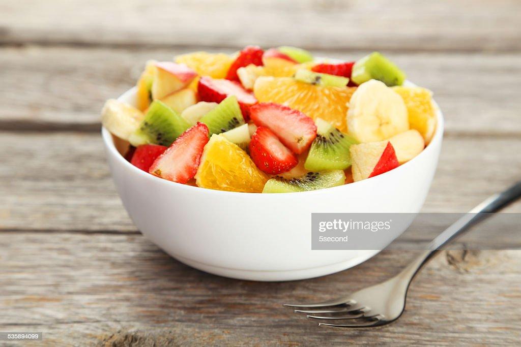 Fresh fruit salad on grey wooden background : Stock Photo