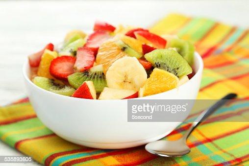 Fresh fruit salad on white wooden background : Stockfoto
