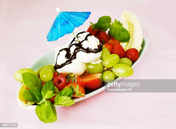 Fresh fruit with vanilla ice cream and cocktail umbrella, elevated view, close-up
