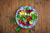 Directly above shot of fresh raw fruits and vegetables salad served in a plate with berries on wooden counter