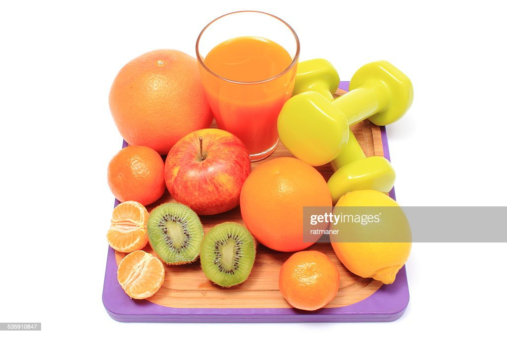 Fresh fruits, dumbbells and glass of juice : Stock Photo