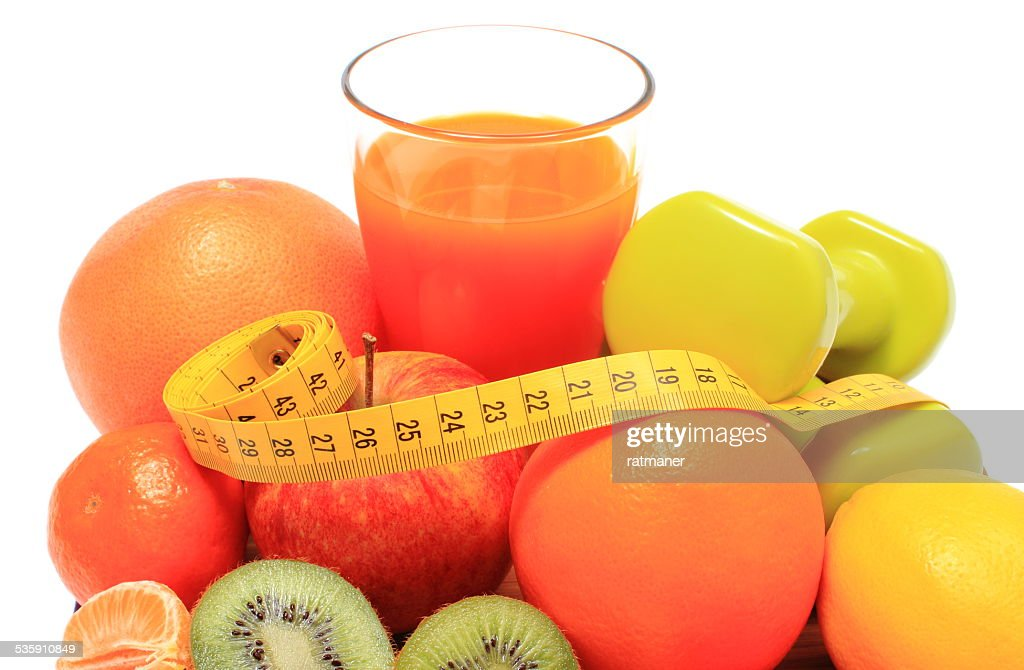 Fresh fruits, dumbbells, tape measure and glass of juice : Stock Photo