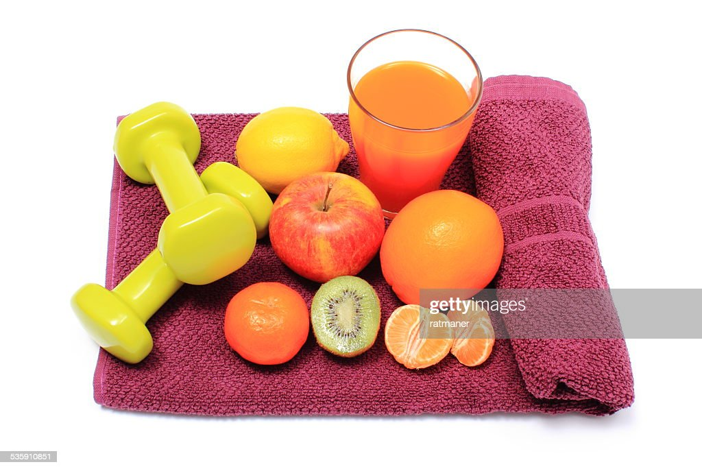 Fresh fruits, glass of juice and dumbbells on purple towel : Stock Photo