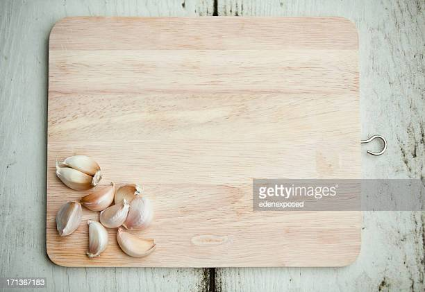 Fresh Garlic ready to chop on wooden chopping board. Overhead.
