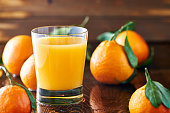 fresh glass of orange juice on rustic table top close up