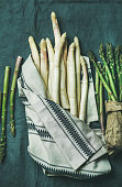 Fresh green and white asparagus in towel over dark grey linen table cloth background, top view