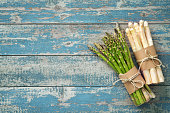 Fresh green and white asparagus with strawberries on wooden background