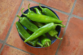 A group or bunch of fresh bright Southwest green chiles, in a round ceramic bowl.  The chiles are freshly washed and have water droplets.  They have names like New Mexican green chiles, Anaheim chile