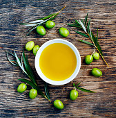 Fresh green olives with leaves and olive oil on wooden background