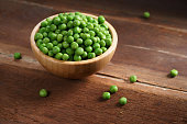 fresh green pea in bowl on wooden background