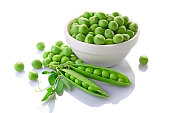 Healthy food. Fresh green peas in white bowl with pink flowers of sweet pea isolated on white background