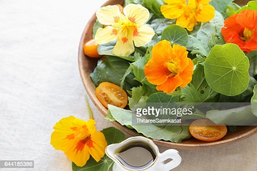 Fresh green salad with edible flowers nasturtium in wooden serving dish : Stock Photo