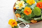Fresh green salad with edible flowers nasturtium in wooden serving dish