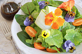 Fresh green salad with edible flowers in white serving dish