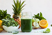 Fresh kale fruit smoothie in a jar with ingredients