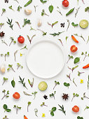 Overhead view fresh herbs and vegetables and empty plate on white background. Text space image.