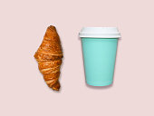 Take away coffee cup and croissant on pink table, top view. Turquoise and pink trendy colors, fresh home made pastry, bright flat lay background with space for text.