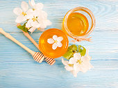 fresh honey, blooming apple tree on wooden background