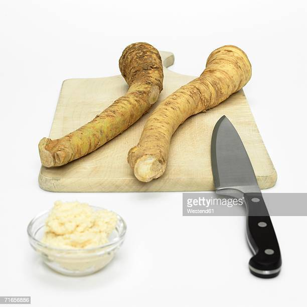 Fresh horseradish with knife and chopping board, close-up