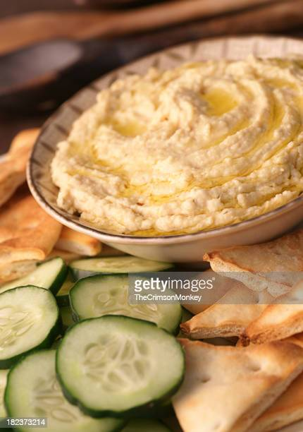 Fresh humus next to slices of cucumber and flatbread