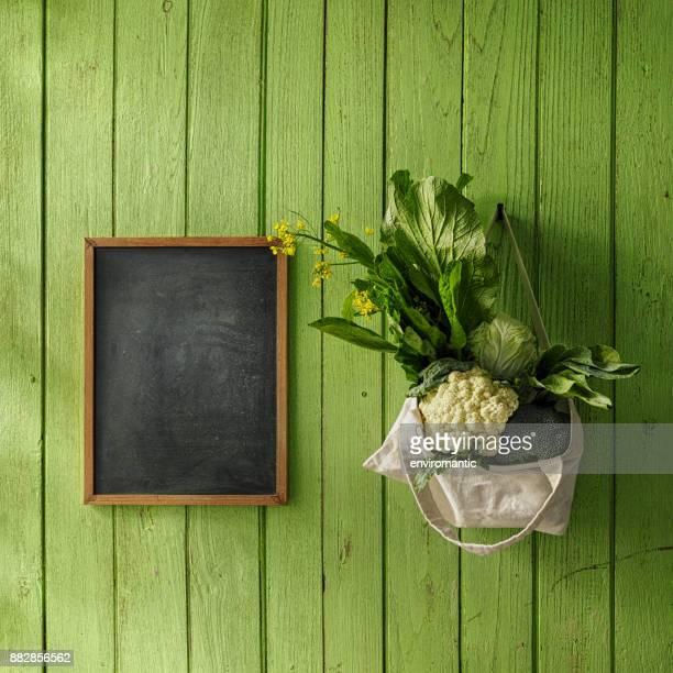 新鮮な緑の葉野菜古いの緑の木板の壁の背景に、黒板の横に、釘から再利用可能なコットン バッグにぶら下がっています。