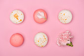 Top view of fresh macarons and Carnation flower on pink surface. Sweet macarons pattern concept