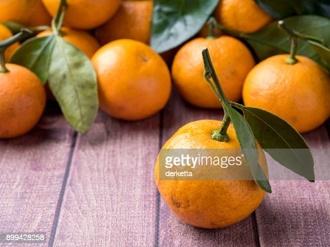 Fresh Mandarin or tangerine with stems and leaves on a brown wooden background copy space : Stock Photo
