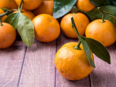 Fresh Mandarin or tangerine with stems and leaves on a brown wooden background copy space.