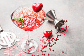 Fresh red margarita cocktail with hearts over gray background, valentine day concepts