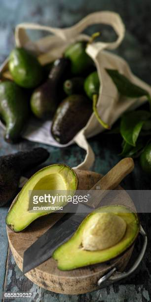 Fresh market avocado cut in half on a wooden cutting board next to a knife with more avocados in the background in a cotton reusable shopping bag.