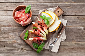 Fresh melon with prosciutto and basil. Antipasti. Top view on wooden table