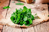 Fresh mint in a bundle, vintage wooden background, selective focus