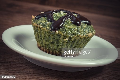 Fresh muffin with spinach, desiccated coconut and chocolate glaze : Stock Photo