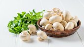 Fresh mushrooms in a clay bowl with parsley leaves on a white wooden table. Vegetarian cuisine. Natural plant food.