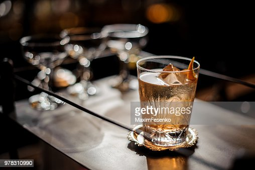 Fresh old fashioned summer cocktail with ice and orange peel : Stock Photo