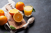 Fresh orange fruits and juice on stone table. View with copy space