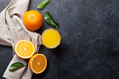 Fresh orange fruits and juice on stone table. Top view with copy space