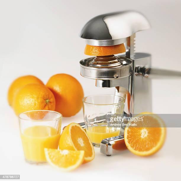 Fresh orange juice alongside an orange juicer