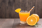 Fresh orange juice and oranges on wooden table.