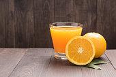 Fresh orange juice and oranges on wooden table.