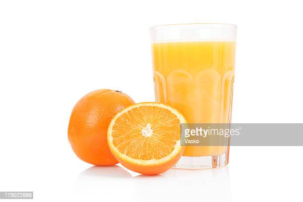 Fresh orange juice in glass cup next to a sliced orange