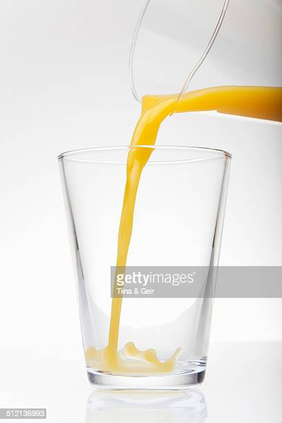 Fresh orange juice pouring from jug into drinking glass