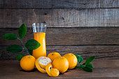 Fresh Oranges and glass of orange juice on the wooden plank / Still life image and selective focus