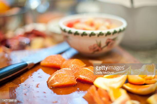 Fresh oranges being peeled and cut for fruit salad
