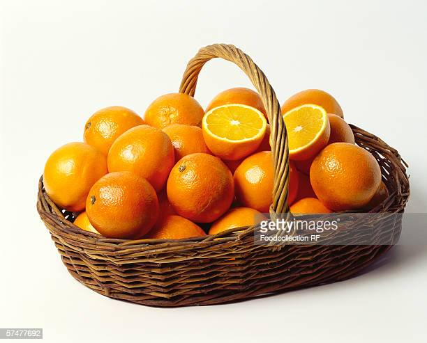 Fresh oranges in a shallow wicker basket
